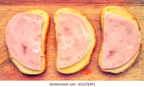 view to wooden desk with three morning sandwiches made with white bred, some butter and thin peaces of sausage. sandwiches with ham as part of breakfast