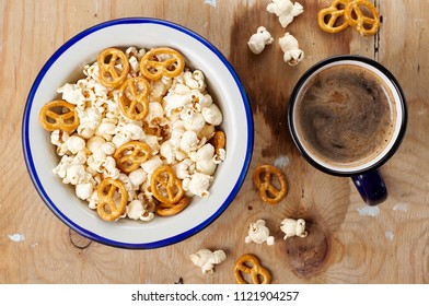 View of a wooden desk top with a cup of coffee and a salted popcorn pretzel snack mix in a bowl. Closeup top view, flat lay