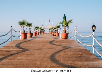 View of a wooden pier with palm trees and a seating area with a chaise longue and a sunshade off the coast of the famous Turkish resort of Side
