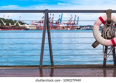 View from wooden pier with safety railing and life buoy to harbor wharf of Keelung, Taiwan