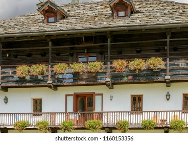 view of wooden walkways of traditional house covered with blossoming geranium flowers, shot on a bright summer day at Gressoney Saint Jean,  Lys valley, Aosta, Italy