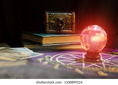 View of wooen casket and crystal balll on the table. Soft focus. Dark tone.