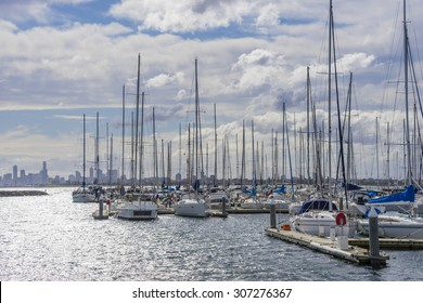 View of yachts or motorboats in floating marina with Melbourne's skyline in the distance