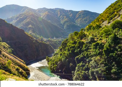 View of Yamuna river and the valley to the village and fields on the background of blue mountain ranges of the Himalayas, near Mussoorie, Uttarakhand, India.