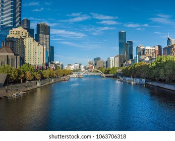 View of Yarra River in Melbourne city with high rise modern buildings along riverbank.