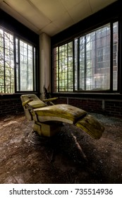A view of a yellow patient / dental chair inside a barred day room at the long abandoned Hudson River State Hospital in New York.