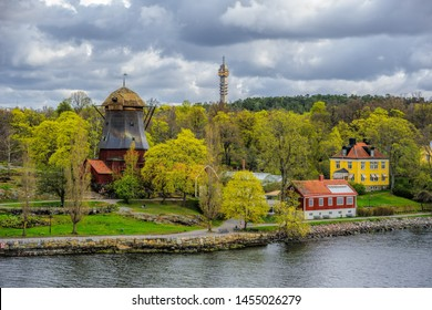 View of yellow and red houses and ancient wind-powered mill painted Falu red without wings on island Djurgarden, Stockholm, Sweden at sunny day. Spring forest and TV tower on background.