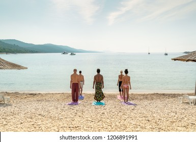 View of yoga group on mats on beach with parasols.