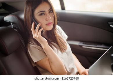 A view of a young Asian Japanese woman is talking on her phone while sitting in the back seat of the private car she booked through a ride hailing app. She looks serious, concerned or focused.
