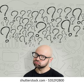View of Young attractive bold man geek with glasses asking question to himself