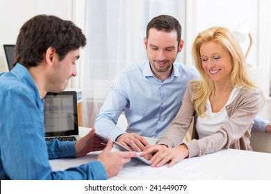 View of a Young attractive couple signing contract on tablet