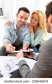 View of Young attractive couple signing contract with real estate agent