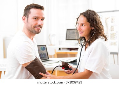 View of a Young attractive doctor checking patient's blood pressure
