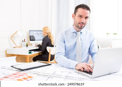 View of a Young attractive engineer working at the office
