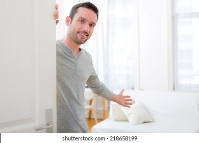 View of a Young attractive man welcoming you in his house