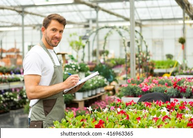 View of a Young attractive man writing notes at the plants nursery