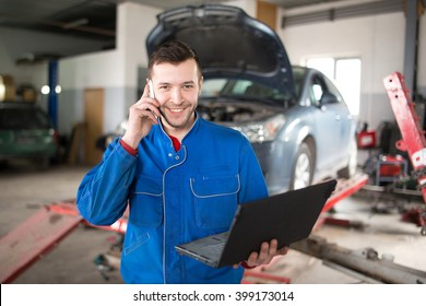 View of a Young attractive mechanic working at the garage. Handsome smiling mechanic.