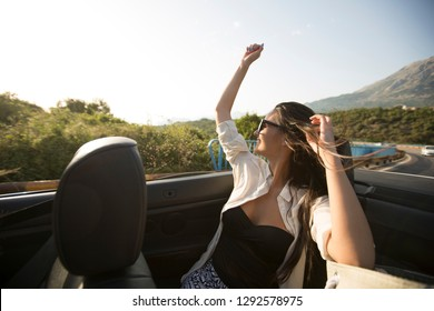 View at young attractive woman drive in cabriolet at seaside
