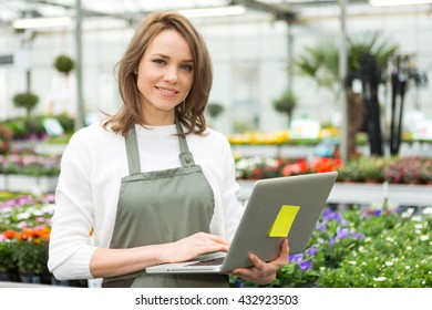 View of a Young attractive woman working at the plants nursery using laptop