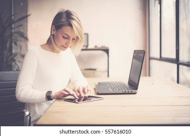 View of young beautiful woman working at the wooden table.Female hands touching tablet on workplace.Concept business people using mobile devices.Horizontal, blurred background