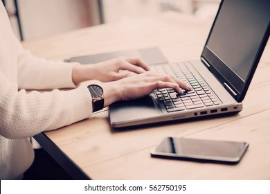 View young businesswoman working at laptop in office.Girl typing on keyboard while sitting her workplace.Horizontal,color filter, blurred background