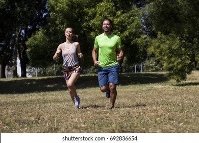 View at young couple running in the park on a sunny day