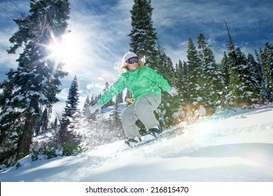 view of a young girl snowboarding in winter environment