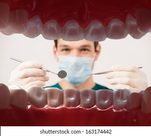 View at young male dentist holding dental tools from patient mouth
