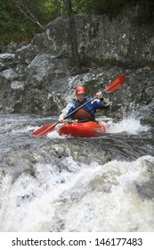 View of a young man kayaking in rough river
