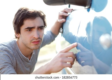 View of a Young man looking for scratches on his car