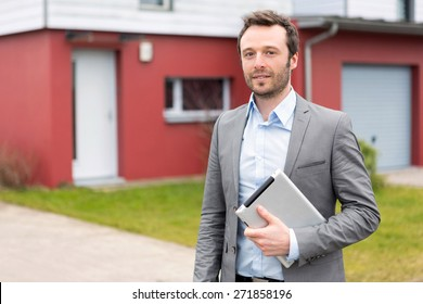 View of a young real estate agent in front of a house