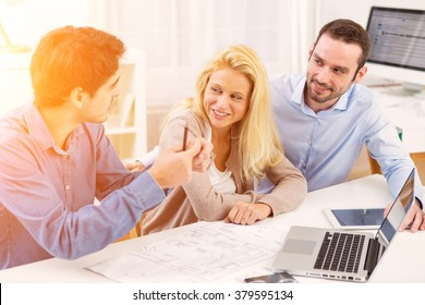 View of a young serious couple meeting a real estate agent