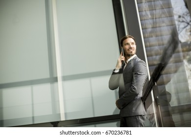 View at Young successful men entrepreneur using mobile phone outdoor