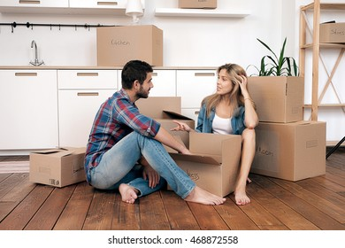 View of young talking couple sitting on floor in kitchen while unpacking boxes