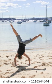 View of a young woman doing backflips and cartwheels along a sandy beach on a sunny summer day with ocean and boats in the background
