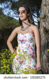 View of a young woman in a floral tight and short dress posing in nature.