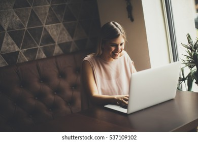 View at young woman with laptop sitting in cafe