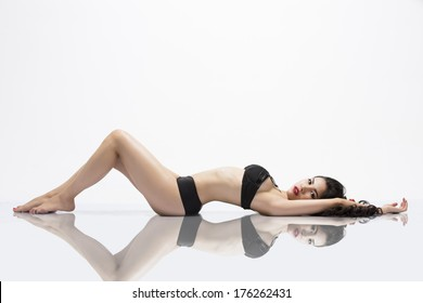 View of a young woman laying down on a reflective surface while wearing black lingerie