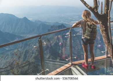 View of young woman looking at the view from sky walk at Tianmen Mountain. It is a mountain located within Tianmen Mountain National Park, Zhangjiajie, in northwestern Hunan Province, China.