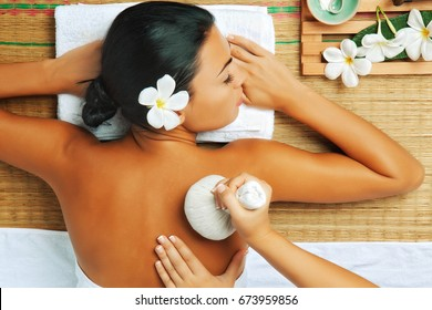 view of young woman in spa environment is being massaged