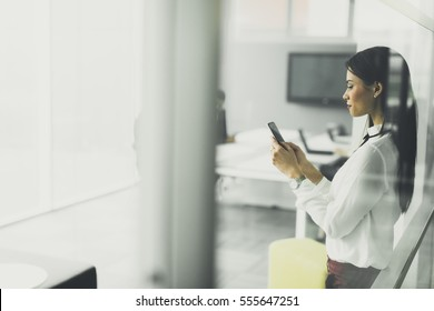 View at young woman using mobile phone in the office