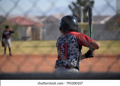 view of youth baseball player through fence