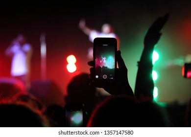 The viewer is filming the concert on the phone
