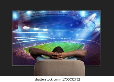 Viewer in front of a large TV relaxed on the armchair at home watching a sports game