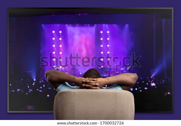 Viewer in front of a large TV relaxed on the armchair at home
