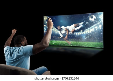Viewer in front of a tv on the armchair at home feels inside the action - Shutterstock ID 1709231644