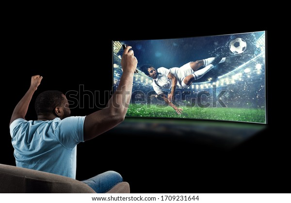 Viewer in front of a tv on the armchair at home feels inside the action