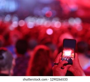 viewer photograps with the mobile phone the performance of a singer during a concert