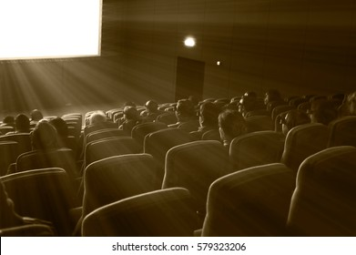 viewers watch 3D motion picture in special glasses, sepia toning