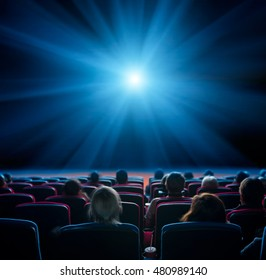 viewers watch blue star at cinema, long exposure, blue glow